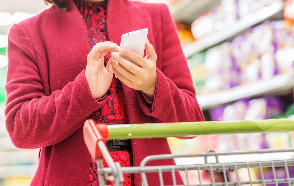 Frau mit Scanner im Supermarkt