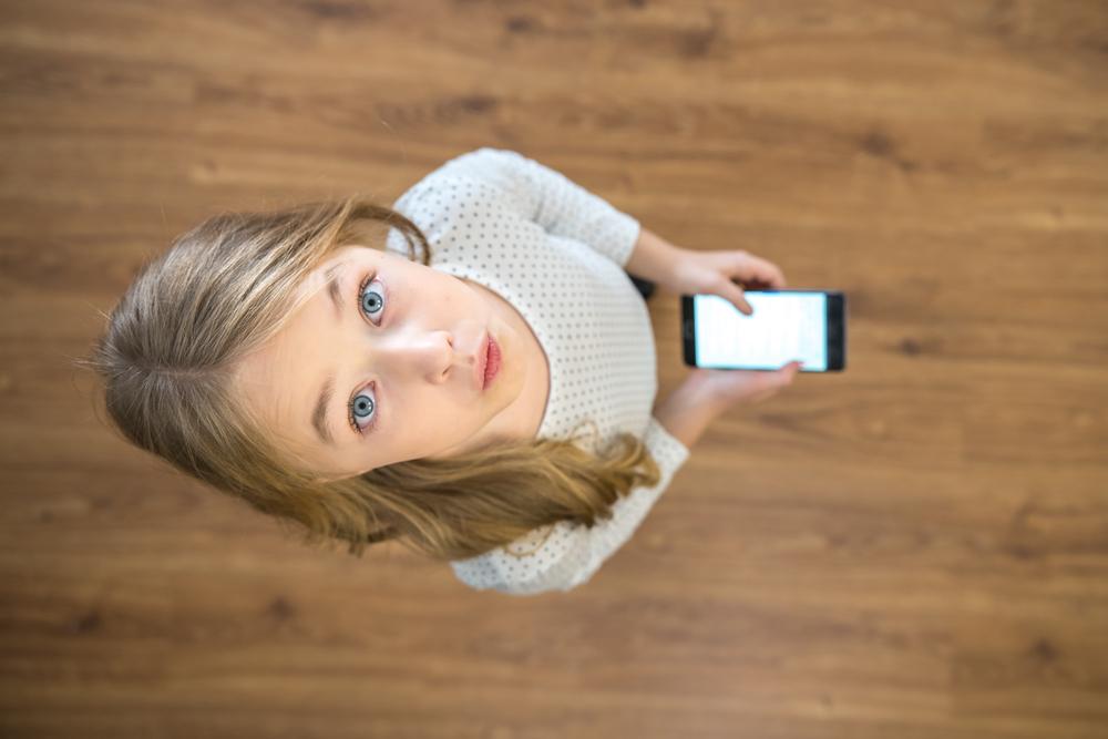 Mädchen aufschauend mit Smartphone