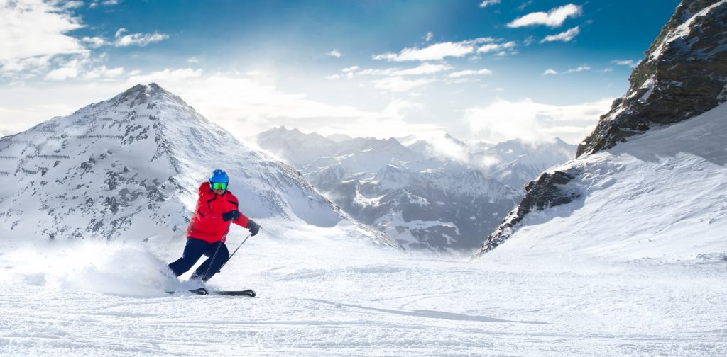 Man skiing on the prepared slope with fresh new powder snow in Alps