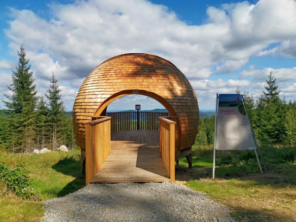 Hier öffnet sich der Blick über die Grenze nach Tschechien. Auf dem Erlebnis-Wanderweg Nebelstein ist er mit VISholo, einem speziellen Aussichtsgerät, inszeniert. Die Wanderer erfahren Wissenswertes über die Orte im Nachbarland.