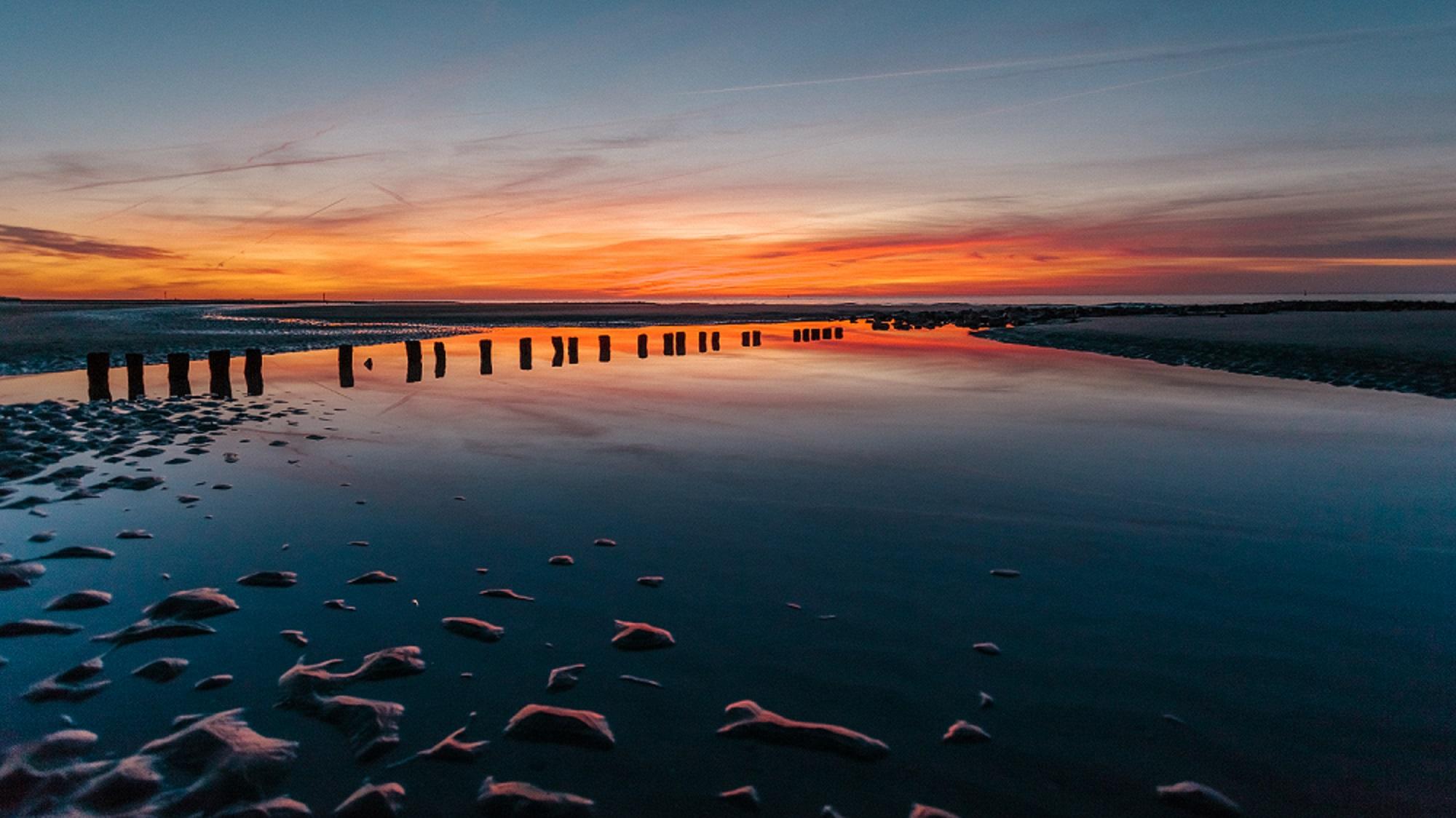 Niedersachsen: Sonnenuntergang spiegelt sich im Wasser eines Priels vor Norderney TM Niedersachsen GmbH Janis Meyer