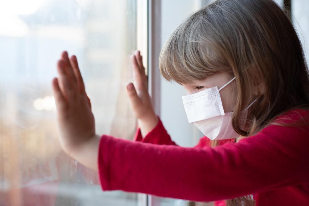 Kind mit Mund-Nasen-Schutz hinter Fenster