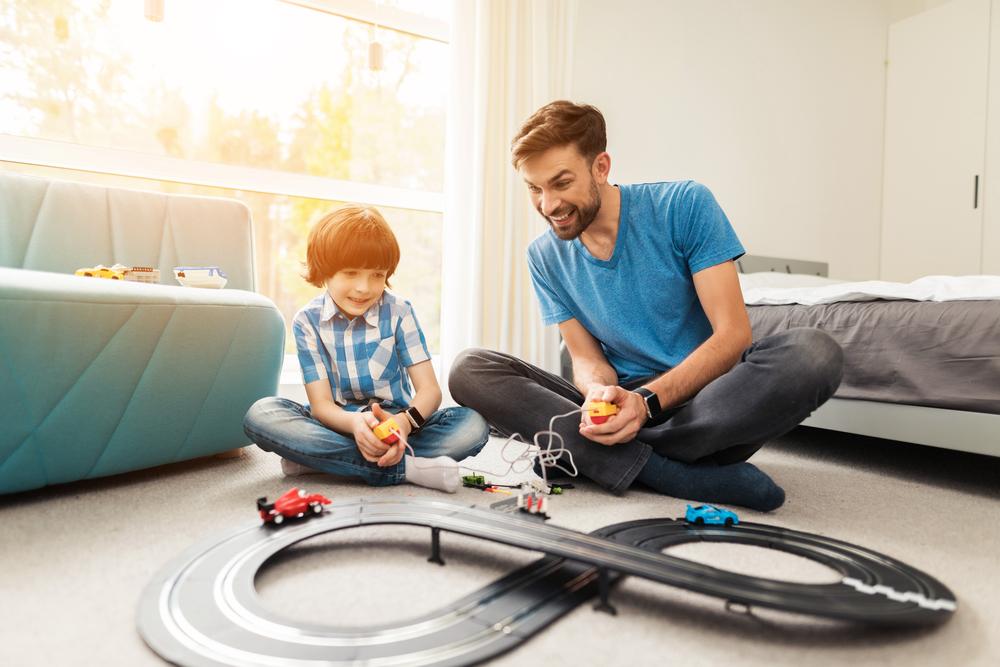 Vater spielt mit Sohn Autorennbahn