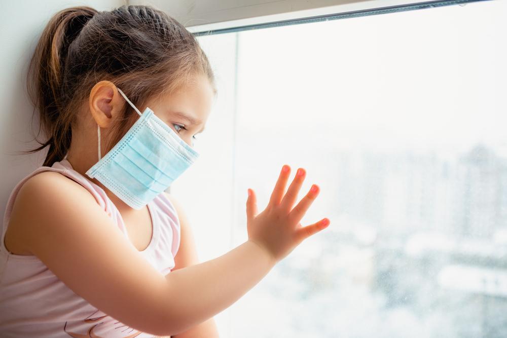 Kind mit Mundnasenschutz hinter Fenster