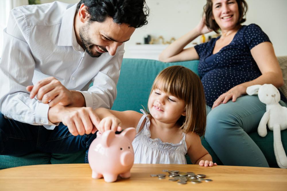 Kind mit Sparschwein und Papa