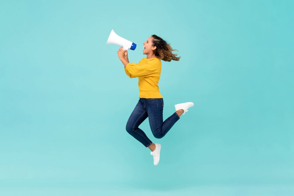 Young African American girl with megaphone jumping and shouting on light blue background; Shutterstock ID 1453338815; Purchase Order: PONS Digital