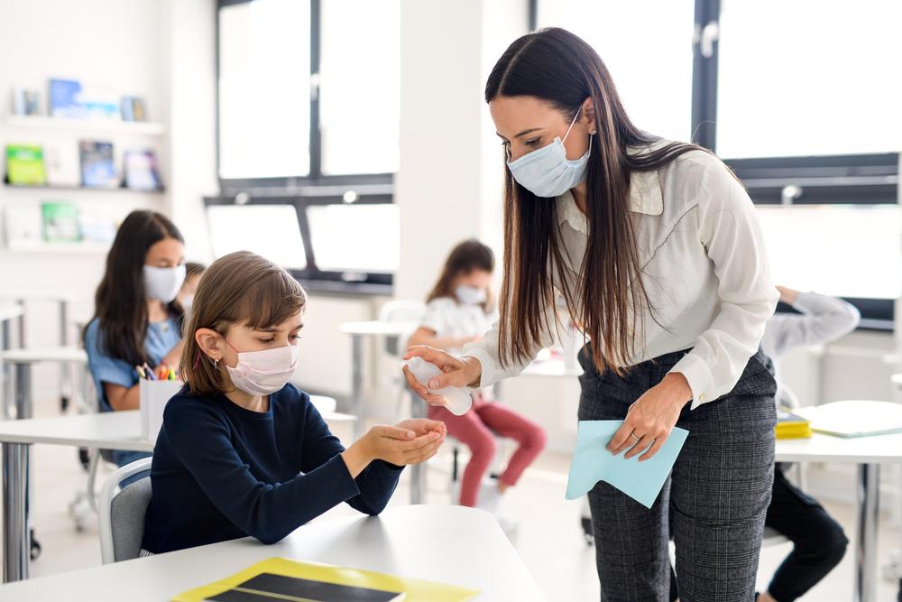 Lehrerin und Schüler mit Mundnasenschutz
