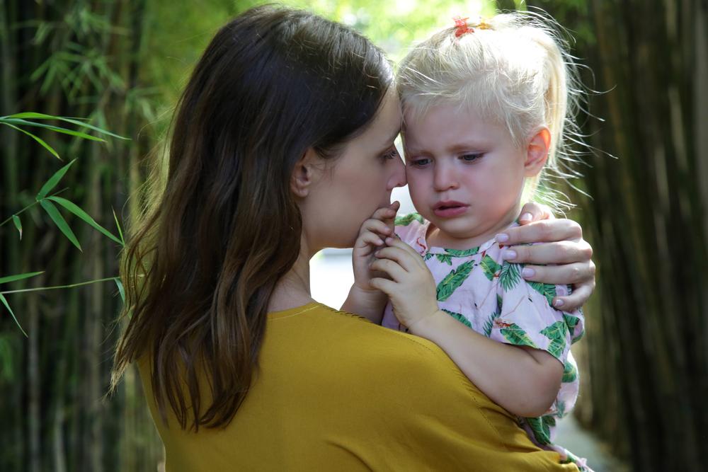 weinendes Kind umarmt Mutter
