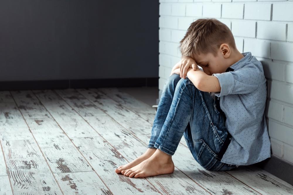 trauriger Bub sitzt am Boden