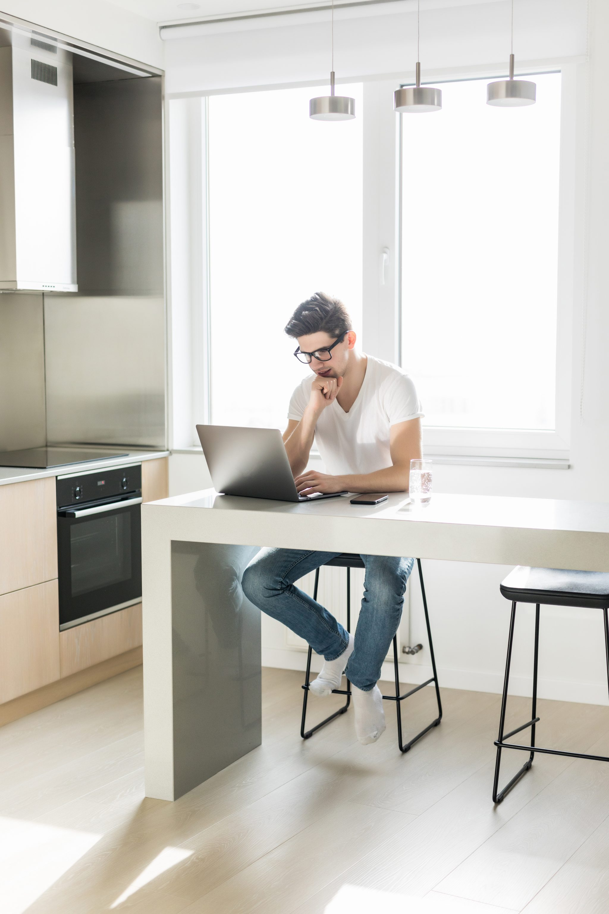Handsome man using a laptop pc in the kitchen
