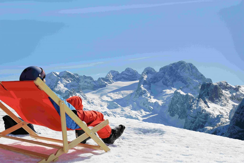 Skier enjoying the nice weather in the deck chair