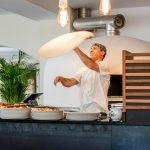 pizzabaecker_beim_zubereiten_von_pizzaboden_c_guenter_standl_hotel_botango