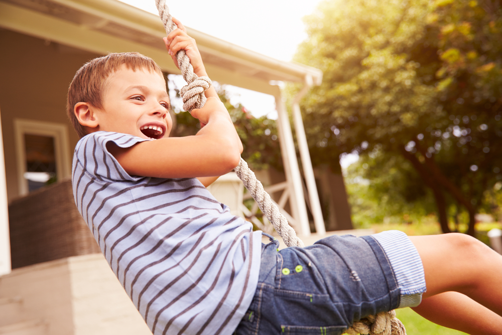 Smiling,Boy,Swinging,On,A,Rope,At,A,Playground