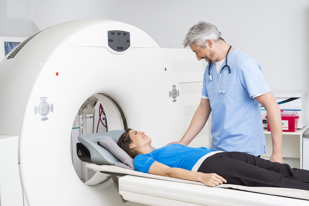 Smiling,Doctor,Talking,To,Patient,Lying,On,Ct,Scan,Machine