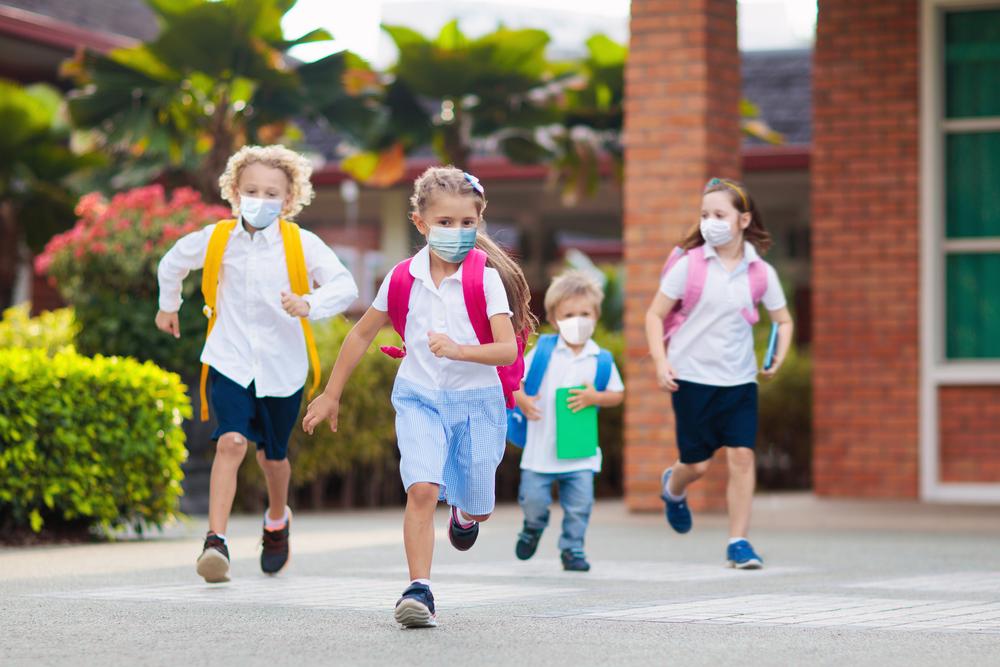 Kinder mit Maske am Schulhof