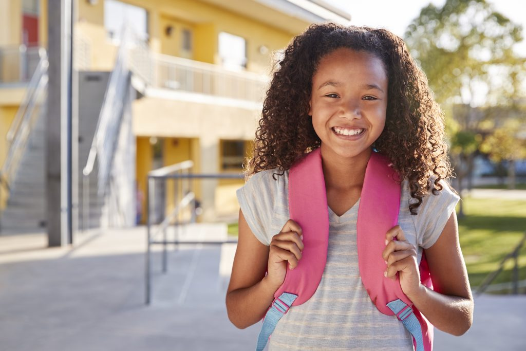 Portrait of smiling elementary school girl with her backpack