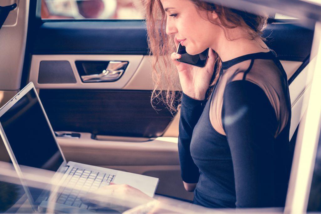 European girl in her car multi-tasking, using her laptop while talking on phone.
