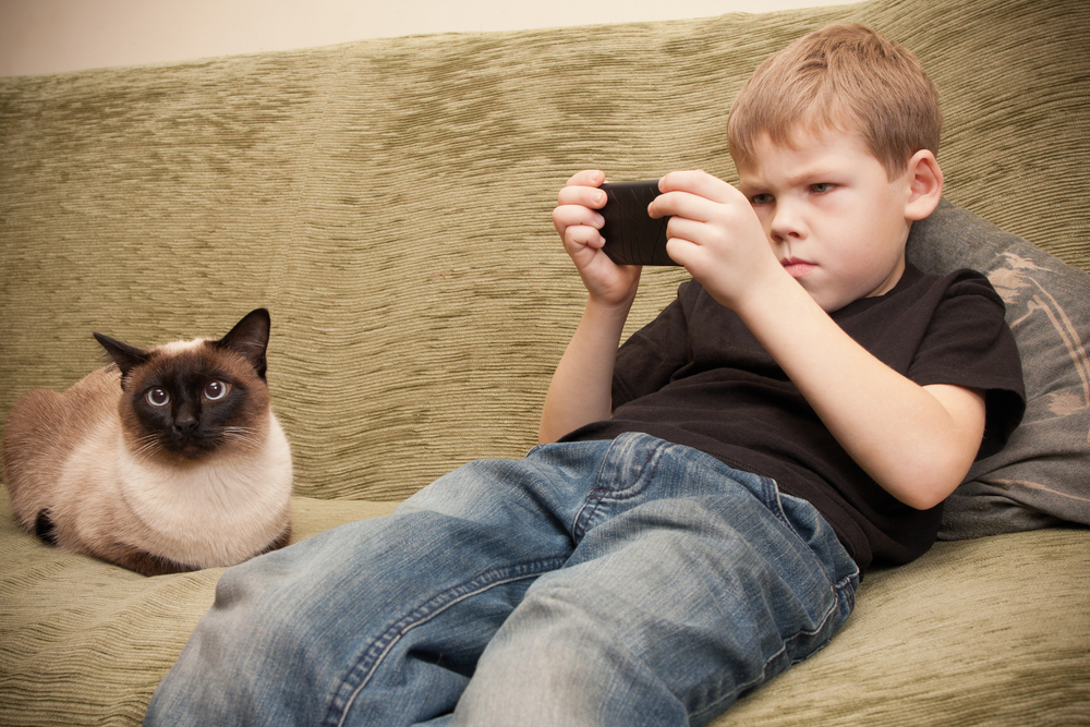 Young,Boy,Playing,Games,With,Your,Mobile,Phone,Or,Reading