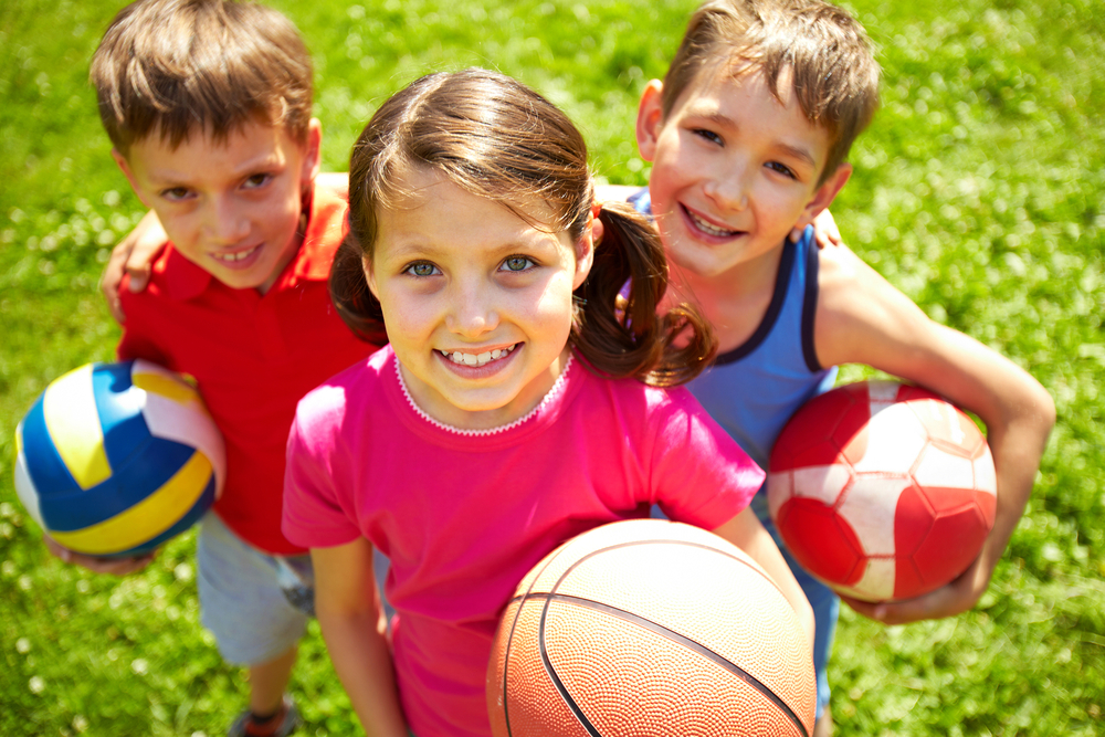 Portrait,Of,Three,Little,Children,With,Balls,Looking,At,Camera