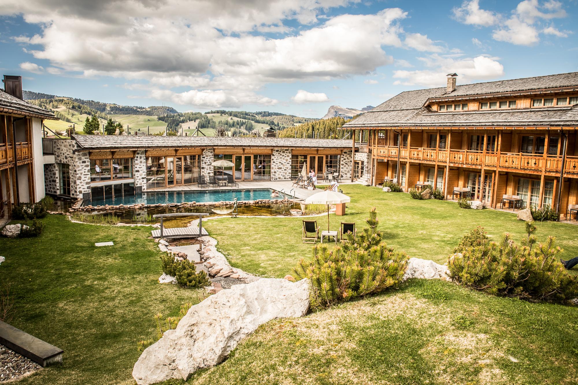 aussenanlage_mit_outdoorpool_im_sommer_tirler-dolomites_living_hotel