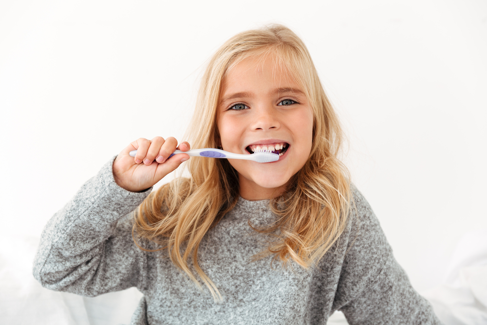 Close-up,Portrait,Of,Female,Kid,Brushing,Her,Teeth,,Looking,At