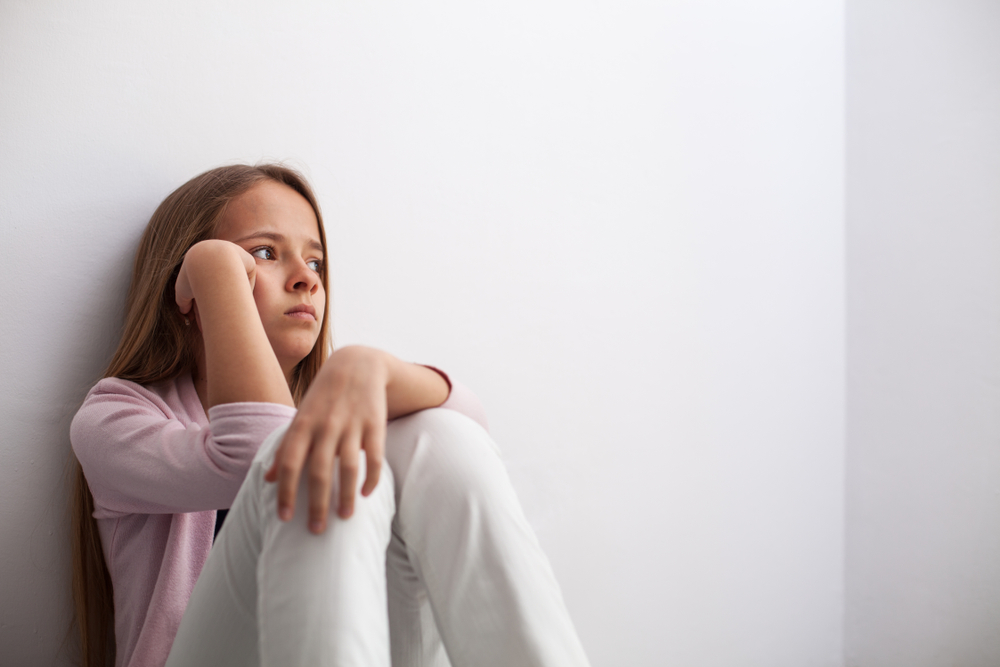 Pensive,Young,Teenager,Girl,Sitting,By,The,Wall,On,The