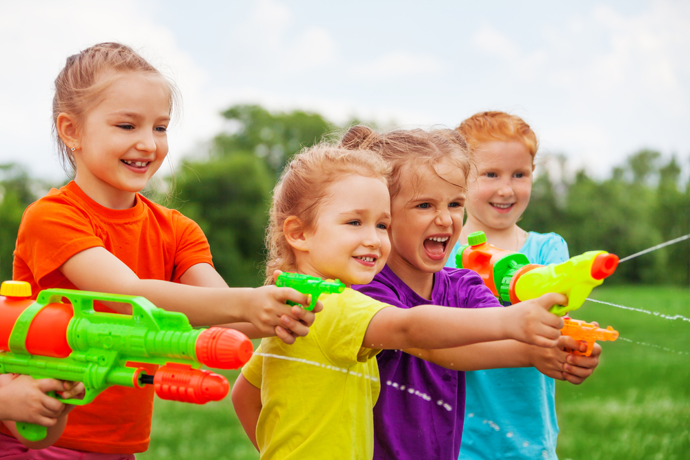 Children,Playing,Outdoors,With,Water,Guns,On,A,Beautiful,Sunny