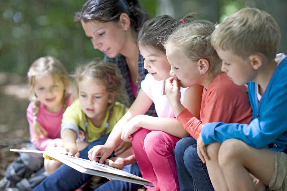 Kindergarten,Teacher,Reading,With,Kids,In,A,Wood,Kindergarten