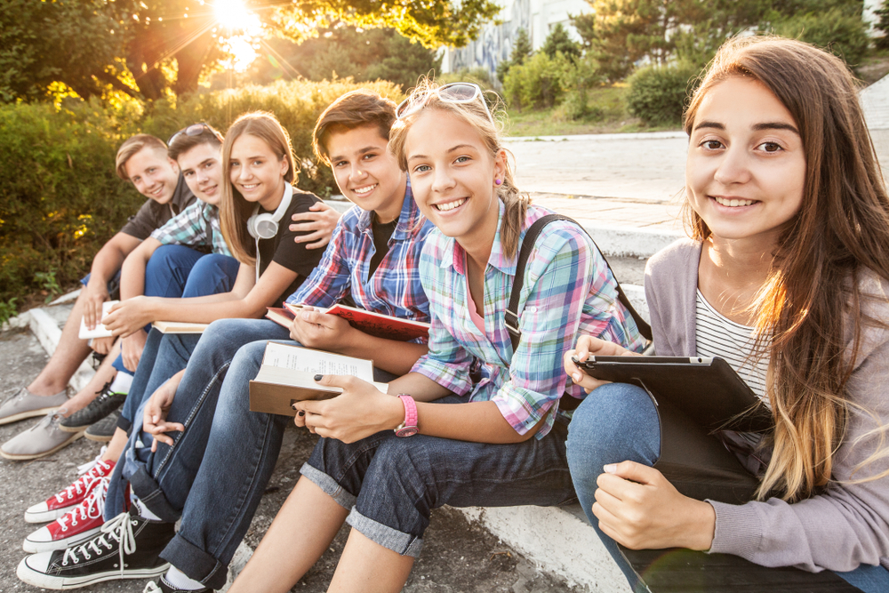 Group,Of,Young,Students,With,Books,And,Gadgets,Sit,On