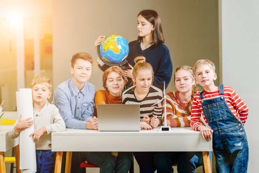 Group,Of,Six,Different,Age,Children,Gathered,Together,Around,Desk