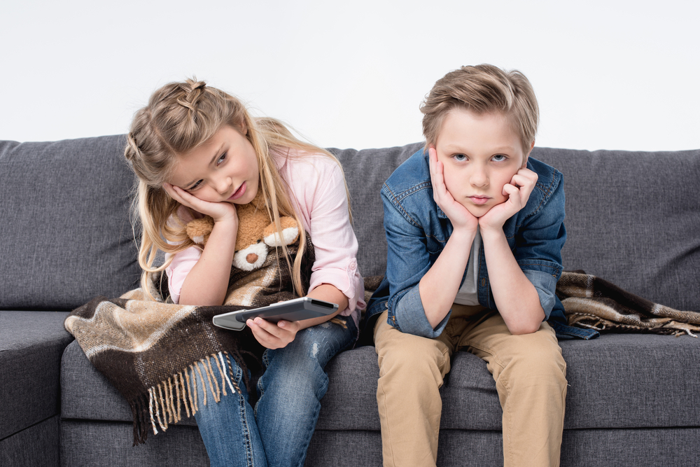 Pre-adolescent,Bored,Brother,And,Sister,Sitting,On,Sofa,And,Holding