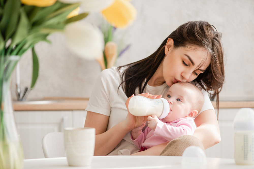 Young,Woman,Kiss,Baby,During,Drinking,Milk