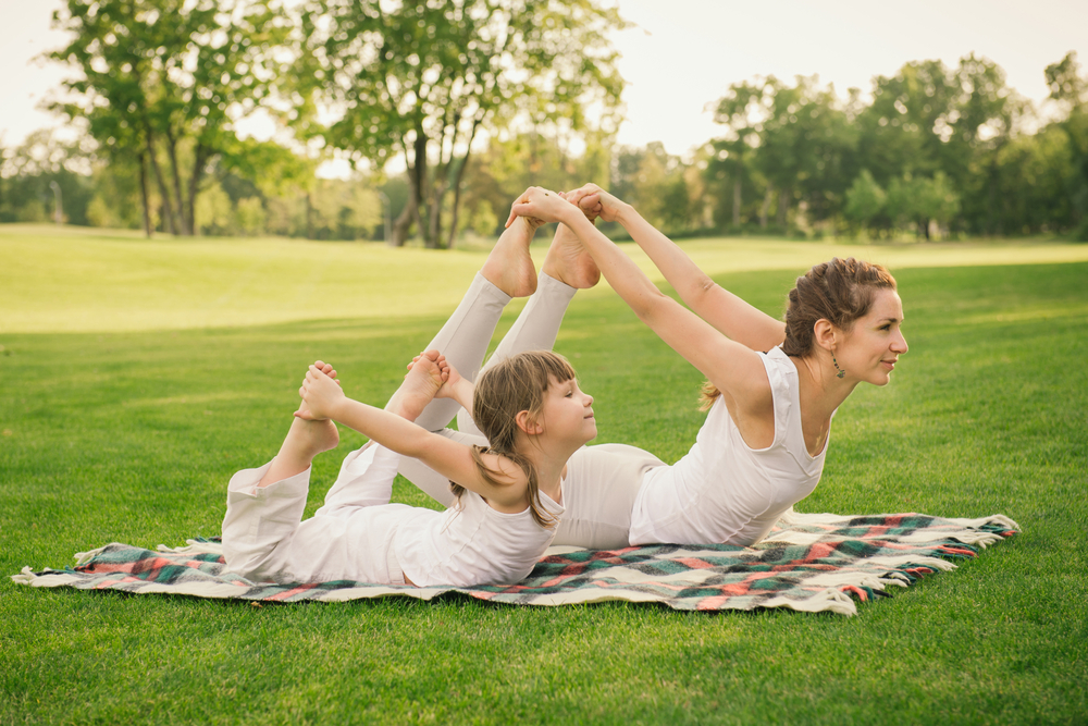 Young,Mother,And,Daughter,Doing,Gymnastics,And,Stretching,In,The